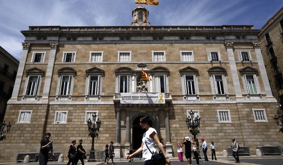 "A banner reading in Catalan: ""Freedom political and exiled prisoners"" hangs from the balcony of the Palau Generalitat, in Sant Jaume square in Barcelona, Spain, Monday, May 27, 2019. The lower chamber of Spain's Parliament on Friday suspended Oriol Junqueras and three colleagues from their recently gained seats as national lawmakers because they are currently in jail during an ongoing trial at Spain's Supreme Court. They face up to 25 years in prison for rebellion charges that stem from a banned referendum and an independence declaration made by the separatist-controlled Catalan government in late 2017. (AP Photo/Manu Fernandez)"
