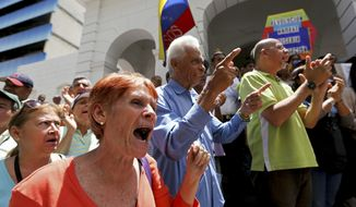Demonstrators shout slogans against Venezuela's President Nicolas Maduro outside the Venezuelan Red Cross headquarters where protesters gathered to demand humanitarian aid in Caracas, Venezuela, Wednesday, May 29, 2019. Demonstrators protested the deaths of several children with leukemia who were awaiting bone marrow transplants, which has ignited a bitter dispute between the government and opponents over who is to blame. (AP Photo/Fernando Llano)