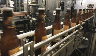 In this Jan. 14, 2019, file photo, bottles, freshly filled with beer, move on a belt at Lakefront Brewery in Milwaukee. At the Strange Brew Festival in Reno, Nev., in May 2019, visitors could sample a peanut butter and pickle pilsner, a tamale lager and a smoked carrot stout. As craft breweries have boomed, competition for attention has intensified. (AP Photo/Carrie Antlfinger, File)