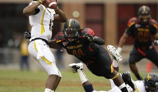 Maryland defensive lineman David Mackall, center, attempts to sack West Virginia quarterback Geno Smith in the second half of an NCAA football game in College Park, Md., Saturday, Sept. 17, 2011. (AP Photo/Patrick Semansky) **FILE**