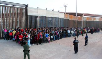 This May 29, 2019, photo released by U.S. Customs and Border Protection (CBP) shows some of 1,036 migrants who crossed the U.S.-Mexico border in El Paso, Texas, the largest that the Border Patrol says it has ever encountered. Video shows them going under a chain-link fence to the U.S., where they waited for agents to come. (U.S. Customs and Border Protection via AP)