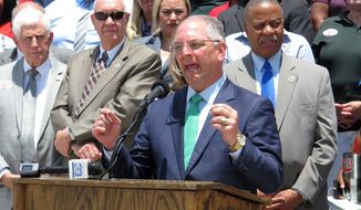 Louisiana Gov. John Bel Edwards, surrounded by public school leaders, speaks in support of the Senate version of next year's K-12 public school financing formula, which includes a $39 million block grant increase for districts, on Wednesday, May 29, 2019, Baton Rouge, La. The House Education Committee debated the formula Thursday, May 30. (AP Photo/Melinda Deslatte)