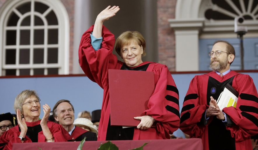 German Chancellor Angela Merkel, center, waves as she is presented with an honorary Doctor of Laws degree as former Harvard President Drew Faust, left, and Harvard Provost Alan Garber, right, applaud during Harvard University commencement exercises, Thursday, May 30, 2019, on the schools campus, in Cambridge, Mass. (AP Photo/Steven Senne)
