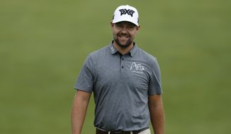 Ryan Moore smiles at his caddie on the 18th hole during the first round of the Memorial golf tournament Thursday, May 30, 2019, in Dublin, Ohio. (AP Photo/Jay LaPrete)
