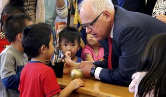 Gov. Tim Walz talks with students Thursday, May 30, 2019 at Bruce Vento Elementary School in St. Paul, Minn. after signing the state's next education budget. The legislation calls for $20 billion in funding for preschool through high school over the next two years. (Christopher Magan/Pioneer Press via AP)