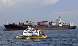 "In this image released by Greenpeace, Greenpeace activists and other environmental organizations display a banner as the cargo ship MV Bavaria, the container vessel allegedly hired to ship back the 69 containers loaded with garbage from Canada, slowly enters the mouth of Subic Bay, Thursday, May 30, 2019 in Subic, Zambales province west of Manila, Philippines. The environmental groups are calling on the Philippine government to ban all waste imports into the country and ratify the Basel Ban Amendment. The banner reads: ""Philippines Is Not A Dumpsite!"" (Greenpeace Via AP)"