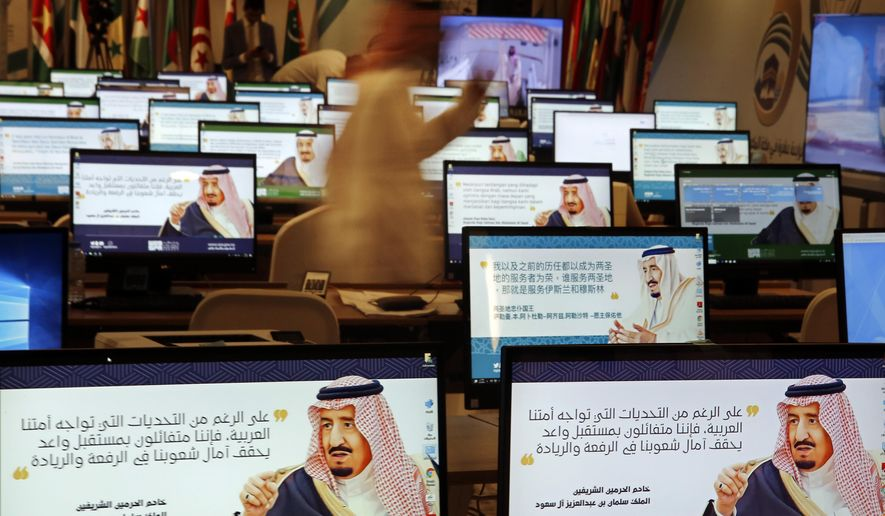 """Screensavers showing King Salman are visible on computers at the press center for upcoming summits, in Mecca, Saudi Arabia, Thursday, May 30, 2019. Salman convenes Arab heads of state from the Gulf and Arab League to discuss escalation in tension with Iran. Arabic on computers reads, """"Despite all the challenges facing our Arab nation. We are optimistic about a promising future that fulfills the hopes of our nations for leadership."""" (AP Photo/Amr Nabil)"""