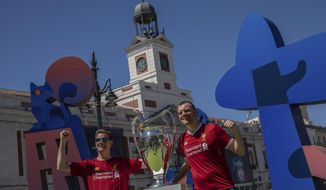 Liverpool supporters pose for a photo next to the Champions League trophy at Puerta del Sol square in downtown Madrid, Spain, Thursday, May 30, 2019. Liverpool and Tottenham were each allocated nearly 17,000 tickets for their fans, but Spanish authorities expect many thousands more to make the trip without tickets or pre-arranged lodging, heightening the possibility of fan trouble around the city. (AP Photo/Bernat Armangue)