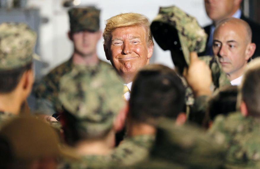 In this Tuesday, May 28, 2019, file photo, U.S. President Donald Trump greets to U.S. servicemen at U.S. Navy multipurpose amphibious assault ship USS Wasp at the U.S. Navy's Yokosuka base in Yokosuka, south of Tokyo. (AP Photo/Eugene Hoshiko, File)