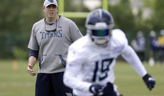 Tennessee Titans offensive coordinator Arthur Smith, left, watches as wide receiver Tajae Sharpe (19) runs a drill during an organized team activity at the Titans' NFL football training facility Tuesday, May 21, 2019, in Nashville, Tenn. (AP Photo/Mark Humphrey)