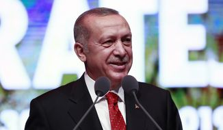 Turkey's President Recep Tayyip Erdogan smiles as he addresses a conference on judicial reform strategy, in Ankara, Turkey, Thursday, May 30, 2019. Erdogan and U.S. President Donald Trump will meet at next month's Group of 20 summit to discuss bilateral issues, including Ankara's plan to buy a Russian missile defense system that has raised the ire of the United States. U.S. officials said the S-400s would pose a risk to Turkey's F-35 fighter jet program and warned Ankara it risked being kicked out of the F-35 program and could face U.S. sanctions. (Presidential Press Service via AP, Pool)