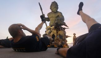 U.S. Navy Chief Petty Officers conduct physical training in front of a statue of Neptune on the oceanfront of Virginia Beach, Va., Friday, Aug. 26, 2011. (AP Photo/Steve Helber) **FILE**