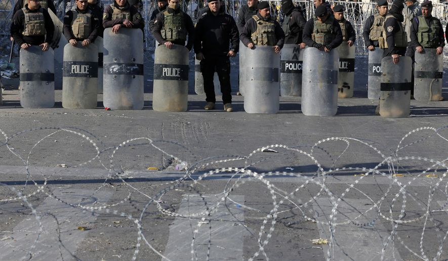 """FILE - In this Feb. 11, 2017 file photo, Iraqi riot police close a bridge leading to the heavily guarded Green Zone during a demonstration of followers of Iraq's influential Shiite cleric Muqtada al-Sadr in Baghdad, Iraq.  The 4-square mile (10-square kilometer), heavily guarded strip on the Tigris River was known as """"Little America"""" following the 2003 U.S.-led invasion that toppled dictator Saddam Hussein. It then became a hated symbol of the country's inequality, fueling the perception among Iraqis that their government is out of touch. (AP Photo/Karim Kadim, File)"""