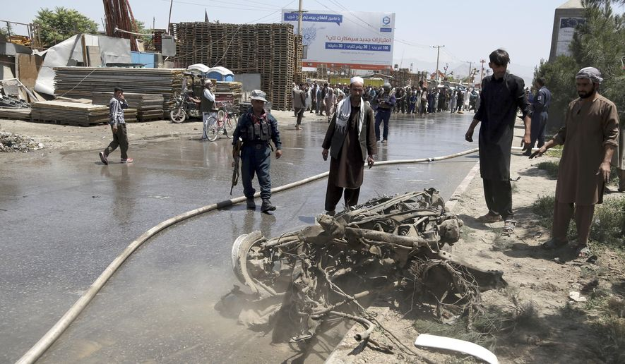 An Afghan police and people stand over the remains of a suicide attacker's vehicle in Kabul, Afghanistan, Friday, May 31, 2019, In a second suicide attack in as many days to rattle the Afghan capital, a car bomb targeting a U.S. convoy exploded early Friday morning in an eastern neighborhood, police said. (AP Photo/Rahmat Gul)