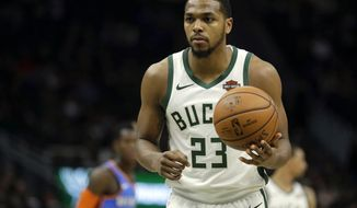 FILE - In this April 10, 2019, file photo, Milwaukee Bucks' Sterling Brown prepares to shoot a free throw during the second half of an NBA basketball game against the Oklahoma City Thunder in Milwaukee. The city of Milwaukee wants to offer Bucks guard Sterling Brown $400,000 to settle his lawsuit alleging that police used excessive force when they used a stun gun to arrest him over a parking violation. The Journal Sentinel reports that the city's Common Council has scheduled a June 10 vote on whether to extend the offer. City attorneys are asking officials to authorize it. (AP Photo/Aaron Gash, File)