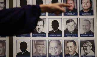 FILE - In this Thursday, Dec. 6, 2018 file photo, a sexual abuse victim points to the photos of Catholic priests accused of sexual misconduct by victims during a news conference in Orange, Calif. On Friday, May 31, 2019, the U.S. Catholic church says that allegations of child sex-abuse by clergy more than doubled in its latest 12-month reporting period, and its spending on victim compensation and child protection surged above $300 million. During the period between July 1, 2017, and June 30, 2018, 1,385 adults came forward with 1,455 allegations of abuse, according to the annual report of the U.S. Conference of Catholic Bishops' Secretariat of Child and Youth Protection. That was up from 693 allegations in the previous year. (AP Photo/Jae C. Hong)