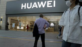In this photo taken Monday, May 20, 2019, a man stands outside a Huawei store in Beijing. The Financial Times reported Friday, May 31, 2019 that tech giant Huawei has ordered its employees to cancel technical meetings with American contacts and has sent home numerous U.S. employees working at its Chinese headquarters. (AP Photo/Ng Han Guan)