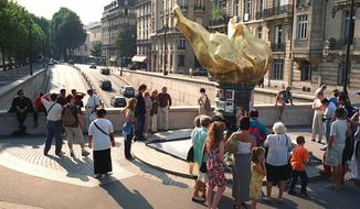 FILE  - In this Thursday, Aug. 31, 2000 file photo, people gather around the gilded statue modeled on the flame of the Statue of Liberty that serves as an unofficial shrine to Princess Diana above the traffic tunnel where she died three years ago in Paris. Paris City Hall wants to name a small plaza after Princess Diana, at the site of the 1997 car crash that killed the cherished British royal. The site already holds a golden flame-shaped monument in her honor, adjacent to the Alma Tunnel where the accident occurred.  (AP Photo/William Alix, File)