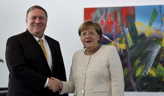 U.S. Secretary of State, Mike Pompeo, left, and German Chancellor Angela Merkel, right, shake hands after a joint statement prior to a meeting at the chancellery in Berlin, Germany, Friday, May 31, 2019. (AP Photo/Michael Sohn)
