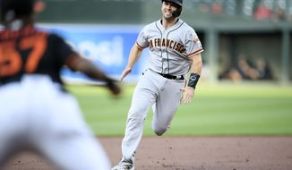 San Francisco Giants' Buster Posey runs to third on a single by Pablo Sandoval during the first inning of a baseball game, Friday, May 31, 2019, in Baltimore. (AP Photo/Nick Wass)