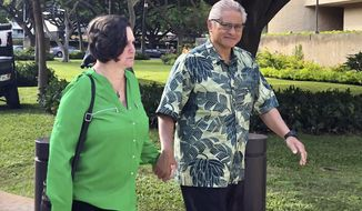 FILE - In this March 12, 2019 file photo, retired Honolulu police chief Louis Kealoha and his wife, former deputy city prosecutor Katherine Kealoha, hold hands while walking to U.S. district court in Honolulu. The public defender who was instrumental in uncovering allegations that a Hawaii law enforcement power couple conspired to frame a relative for a mailbox theft says he was suspicious about how easily it appeared to be removed in surveillance footage. Federal defender Alexander Silvert is testifying in the trial of the Kealohas. Silvert represented the uncle the Kealohas allegedly framed. (AP Photo/Jennifer Sinco Kelleher, File)