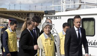 Kang Kyung-wha, center, foreign minister of South Korea, together with her Hungarian counterpart, Peter Szijjarto, right, visits the bank of the Danube River close to Margit Bridge where a sightseeing boat capsized in Budapest, Hungary, Friday, May 31, 2019. Hungarian police have detained the captain of a cruise ship that collided with the sightseeing boat packed with South Korean tourists, causing it to sink quickly in the river in Budapest, as loved ones of the missing and dead were expected to arrive Friday in Hungary. (AP Photo/Marko Drobnjakovic)