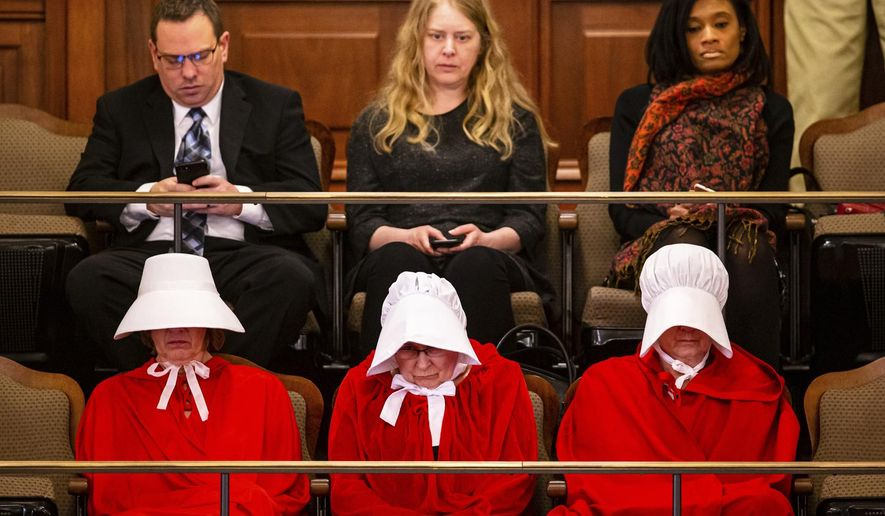 """People dressed as characters from """"The Handmaid's Tale"""" sit in the the president's gallery of the Senate showing their support of the Reproductive Health Act on the last scheduled day of the spring session at the State Capitol, Friday, May 31, 2019, in Springfield, Ill. (Justin Fowler/The State Journal-Register via AP)"""