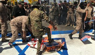 "Iraqi Popular Mobilization Forces burn representations of U.S. and Israeli flags during ""al-Quds"" Day, Arabic for Jerusalem, in Baghdad, Iraq, Friday, May 31, 2019. Jerusalem Day began after the 1979 Islamic Revolution in Iran, when the Ayatollah Khomeini declared the last Friday of the Muslim holy month of Ramadan a day to demonstrate the importance of Jerusalem to Muslims. (AP Photo/Ali Abdul Hassan)"