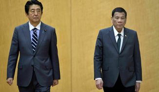 Japan's Prime Minister Shinzo Abe, left, and Philippines President Rodrigo Duterte attend a welcoming prior to their meeting at Abe's official residence Friday, May 31, 2019, in Tokyo. Duterte is in Japan to participate in the 25th International Conference on the Future of Asia in Tokyo. (David Mareuil/Pool Photo via AP)