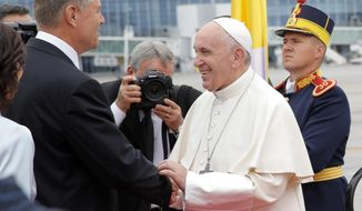 Pope Francis is welcomed by Romanian President Klaus Iohannis, left, upon his arrival from Rome at Henri Coanda International Airport in Otopeni, near Bucharest, Romania, Friday, May 31, 2019. Pope Francis is heading to Romania for a three-day, cross-country pilgrimage that in many ways is completing the 1999 trip by St. John Paul II that marked the first-ever papal visit to a majority Orthodox country. (AP Photo/Vadim Ghirda)