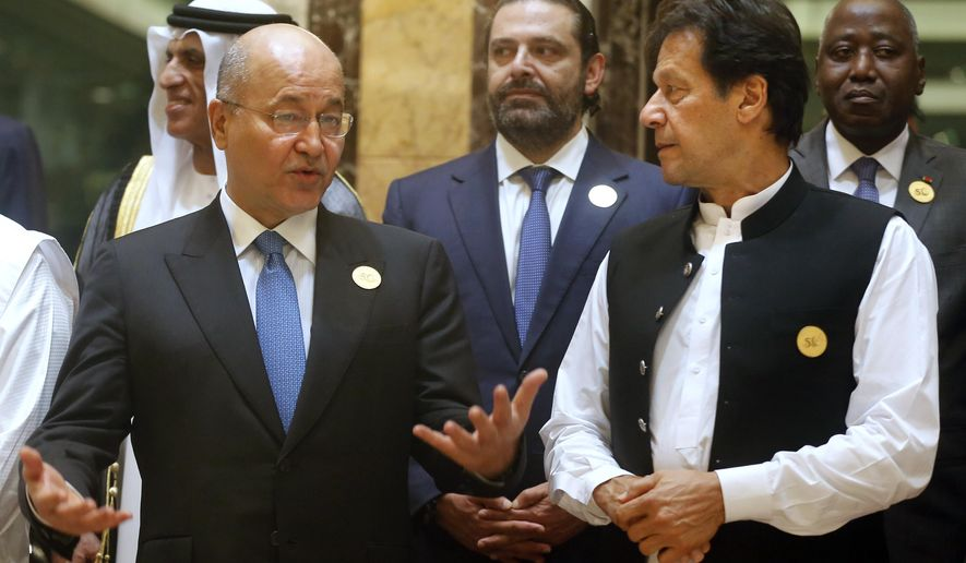 Pakistan's Prime Minister Imran Khan, right, listens to Iraq's President Barham Salih during a group picture ahead of Islamic Summit of the Organization of Islamic Cooperation (OIC) in Mecca, Saudi Arabia, early Saturday, June 1, 2019. Muslim leaders from some 57 nations gathered in Islam's holiest city of Mecca late Friday to discuss a breadth of critical issues ranging from a spike in tensions in the Persian Gulf, to Palestinian statehood, the plight of Rohingya refugees and the growing threat of Islamophobia. (AP Photo/Amr Nabil)