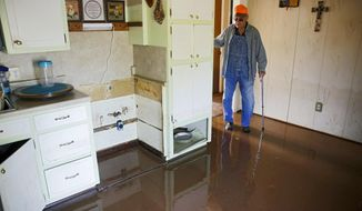 In this Thursday, May 30, 2019 photo, Eugene Bowers looks at the kitchen in his flooded home in the Town and Country neighborhood west of Sand Springs, Okla. (Mike Simons/Tulsa World via AP)