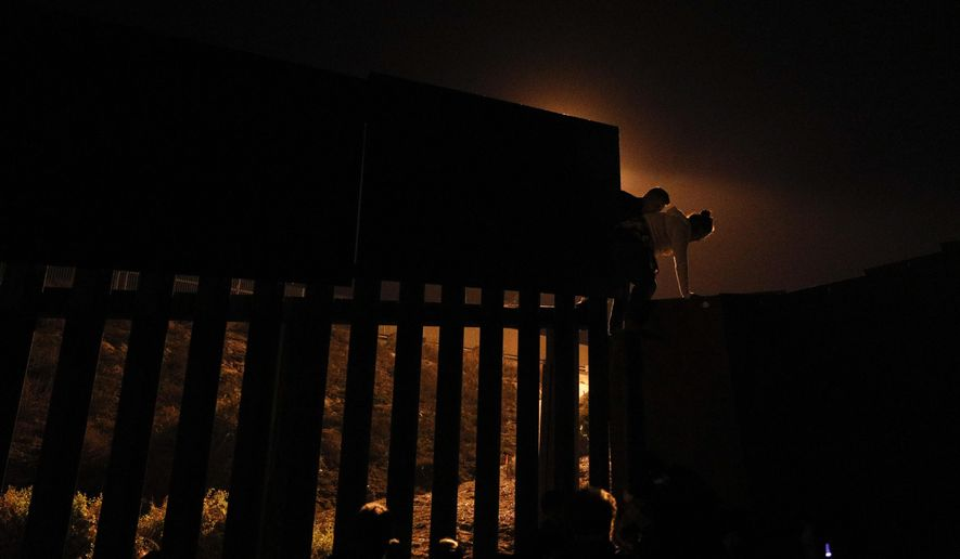 FILE - In this Dec. 2, 2018, file photo taken from Playas of Tijuana, Mexico, Honduran migrants climb over a section of the U.S. border fence before turning themselves in to border control agents. As Trump threatens tariffs, U.S. authorities are overstretched and overwhelmed by an unprecedented surge of Central American migrant families arriving at the border with Mexico. (AP Photo/Rebecca Blackwell, File)