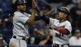 Minnesota Twins' Jorge Polanco (11) celebrates with Jonathan Schoop after they both scored on a single by Eddie Rosario off Tampa Bay Rays relief pitcher Adam Kolarek during the ninth inning of a baseball game Friday, May 31, 2019, in St. Petersburg, Fla. (AP Photo/Chris O'Meara)