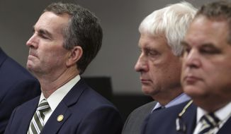 "Virginia Gov/ Ralph Northam, left, listens during a news conference in Virginia Beach, Va. Friday, May 31, 2019. A longtime city employee opened fire in a municipal building in Virginia Beach on Friday, killing several people on three floors and sending terrified co-workers scrambling for cover before police shot and killed him following a ""long gun-battle,"" authorities said. (AP Photo/Vicki Cronis-Nohe)"