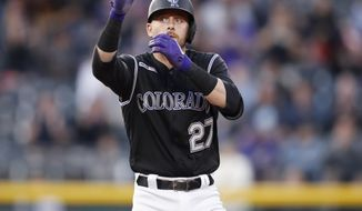 Colorado Rockies' Trevor Story gestures to the dugout after hitting a double to drive in three runs off Toronto Blue Jays starting pitcher Edwin Jackson in the third inning of a baseball game Friday, May 31, 2019, in Denver. (AP Photo/David Zalubowski)