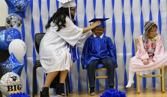In this photo taken May 16, 2019, Denise Kalmakoff shares the stage with the school's incoming kindergarteners, Joseph Amodo White and Serenity Simeonoff during a graduation ceremony in Akhiok, Alaska. Across Alaska, lots of teens felt the stress of lunging toward the high school finish line this month, but Kalmakoff felt a pressure known to just a few. In Akhiok, an Alutiiq village of about 52 people, all eyes were on her. She was her school's entire graduating class. (Marc Lester/Anchorage Daily News via AP)