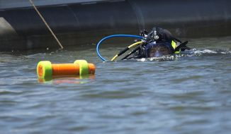 In this May 15, 2019 photo, diver Bill Waldrop enters the water, part of a crew working on a project to reassess shipwrecks from the Revolutionary War in Yorktown, Va. For the first time in 30 years the group is actually diving on the wrecks in the York River. (L. Todd Spencer/The Virginian-Pilot via AP)