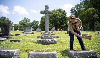 Ty Smith cleans off a headstone at Calvary Cemetery Saturday, May 18, 2019, in Nashville, Tenn. Through his Eagle Scout project of documenting headstones, people will be able locate and find information about ancestors through BillionGraves.  (Courtney Pedroza/The Tennessean via AP)