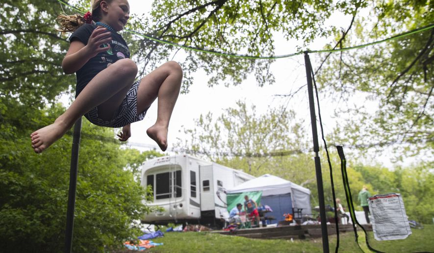 Ava Schoville of Percival, Iowa jumps on her neighbor's trampoline outside of their RV at the Waubonsie State Park in Hamberg, Iowa. (Elsie Stormberg/Omaha World-Herald via AP)