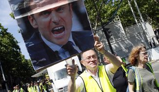 Yellow vest protester holds a placard with a portrait of French President Emmanuel Macron during a march, in Paris, Saturday, June 1, 2019. Yellow vest protests are taking place for the 29th consecutive week to challenge President Emmanuel Macron's economic policies. (AP Photo/Francois Mori) ** FILE **