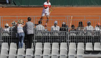 Two spectators watch a match from an adjacent court at the French Open tennis tournament at the Roland Garros stadium in Paris, Saturday, June 1, 2019. (AP Photo/Michel Euler)