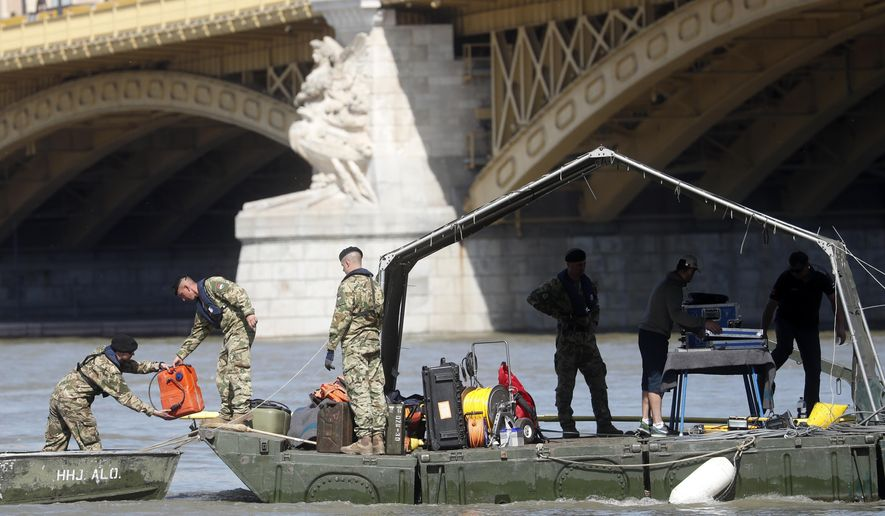 Rescue team members are seen on a barge floating on the Danube river where a sightseeing boat capsized in Budapest, Hungary, Saturday, June 1, 2019. As divers descended Friday into the Danube, Hungarian authorities predicted it would take an extended search to find the 21 people still missing after a boat carrying South Korean tourists was rammed by a cruise ship and sank into the river in Budapest. (AP Photo/Laszlo Balogh)