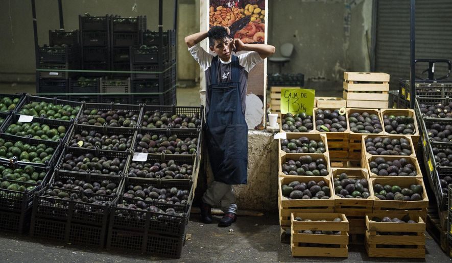 FILE - In this Aug. 9, 2016 file photo, an avocado vendor talks on his cellphone at a market in Mexico City.  Summary:The potential Trump tariffs are expected to hit U.S. avocado lovers more than Mexican producers. (AP Photo/Nick Wagner, File)