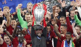 Liverpool coach Juergen Klopp lifts up the trophy as he celebrates with players after winning the Champions League final soccer match between Tottenham Hotspur and Liverpool at the Wanda Metropolitano Stadium in Madrid, Saturday, June 1, 2019. (AP Photo/Armando Franca)