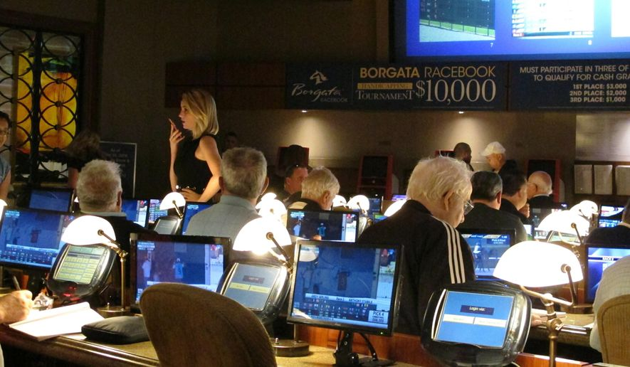FILE - This June 14, 2018 file photo shows bettors waiting to make wagers on sporting events at the Borgata casino in Atlantic City hours after it began accepting sports bets. It's hard enough for compulsive gamblers to stop betting. Now, in a growing number of places, they're being bombarded with ads urging them to bet on sports. It's a temptation they didn't face a year ago. And it's raising questions as to how tightly regulated sports betting advertising should be in the United States.  (AP Photo/Wayne Parry)