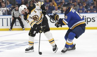 Boston Bruins center Patrice Bergeron (37) passes the puck away from St. Louis Blues defenseman Jay Bouwmeester (19) during the first period of Game 3 of the NHL hockey Stanley Cup Final Saturday, June 1, 2019, in St. Louis. (AP Photo/Jeff Roberson)