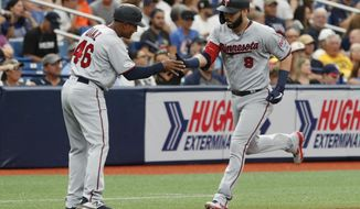 Minnesota Twins' Marwin Gonzalez, right, celebrates with third base coach Tony Diaz after hitting a home run against the Tampa Bay Rays during the fifth inning of a baseball game Saturday, June 1, 2019, in St. Petersburg, Fla. (AP Photo/Scott Audette)