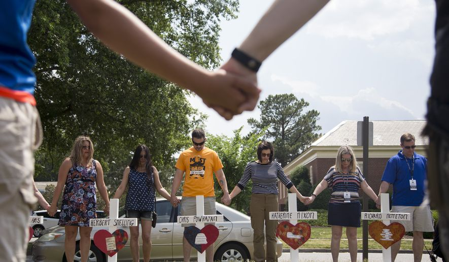 Community members hold hands and pray around the 12 crosses at the memorial located by Building 11 of the Municipal Center, Sunday, June 2, 2019, in Virginia Beach, Va. Twelve crosses were placed at the memorial to honor the 12 victims of the mass shooting that took place at the Virginia Beach Municipal Center days earlier. (Sarah Holm/The Virginian-Pilot via AP)