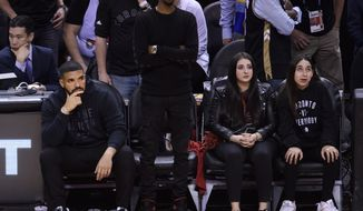 Rapper Drake, Left, looks on from his seat as the Toronto Raptors play the Golden State Warriors during the second half of Game 2 of basketballs NBA Finals, Sunday, June 2, 2019, in Toronto. (Nathan Denette/The Canadian Press via AP)